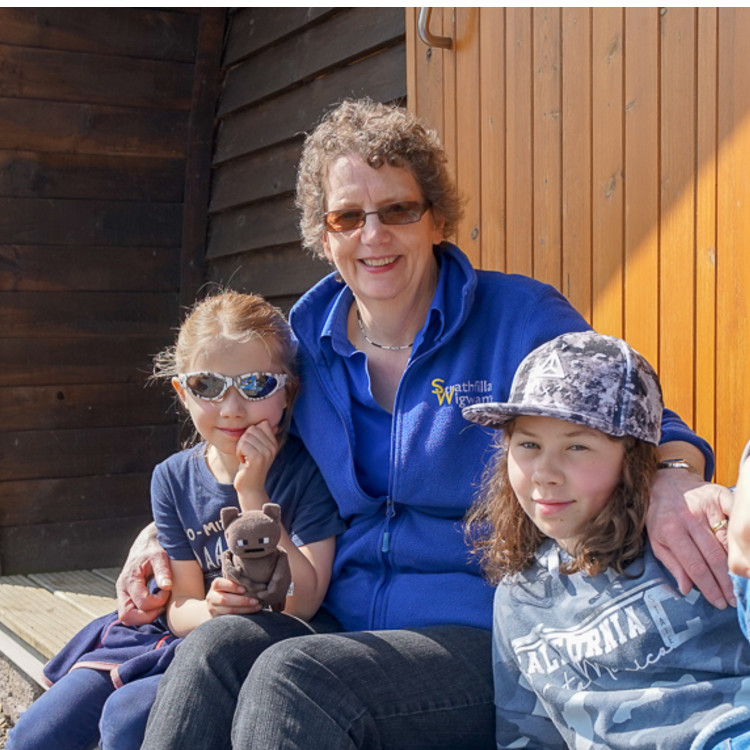 Rena and her grandchildren outside one of the wigwams, on a sunny day.